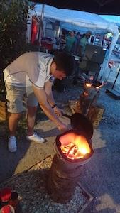 mann, offene feuerstelle in metallbox, pfanne, grill- und genussfestival wien