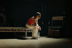 Rami Malek als Freddie Mercury, sitzt, vor Konzert