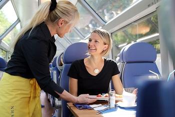 Frau bekommt Frühstück serviert im Panoramawagen der Mariazellerbahn