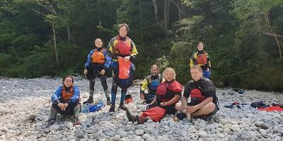 Wildwasser-Kajakkurs-Gruppe mit Ausrüstung an Land