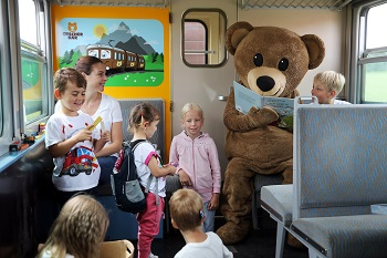Spielwagen im Ötscherbär, Kinder mit Büchern und Maskottchen