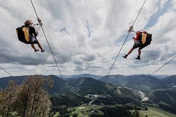 2 Personen auf der Zipline in Annaberg, Bergpanorama