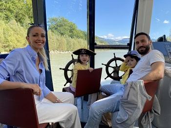 Familie bei einer Schifffahrt auf der Salzach, Kinder am Steuer
